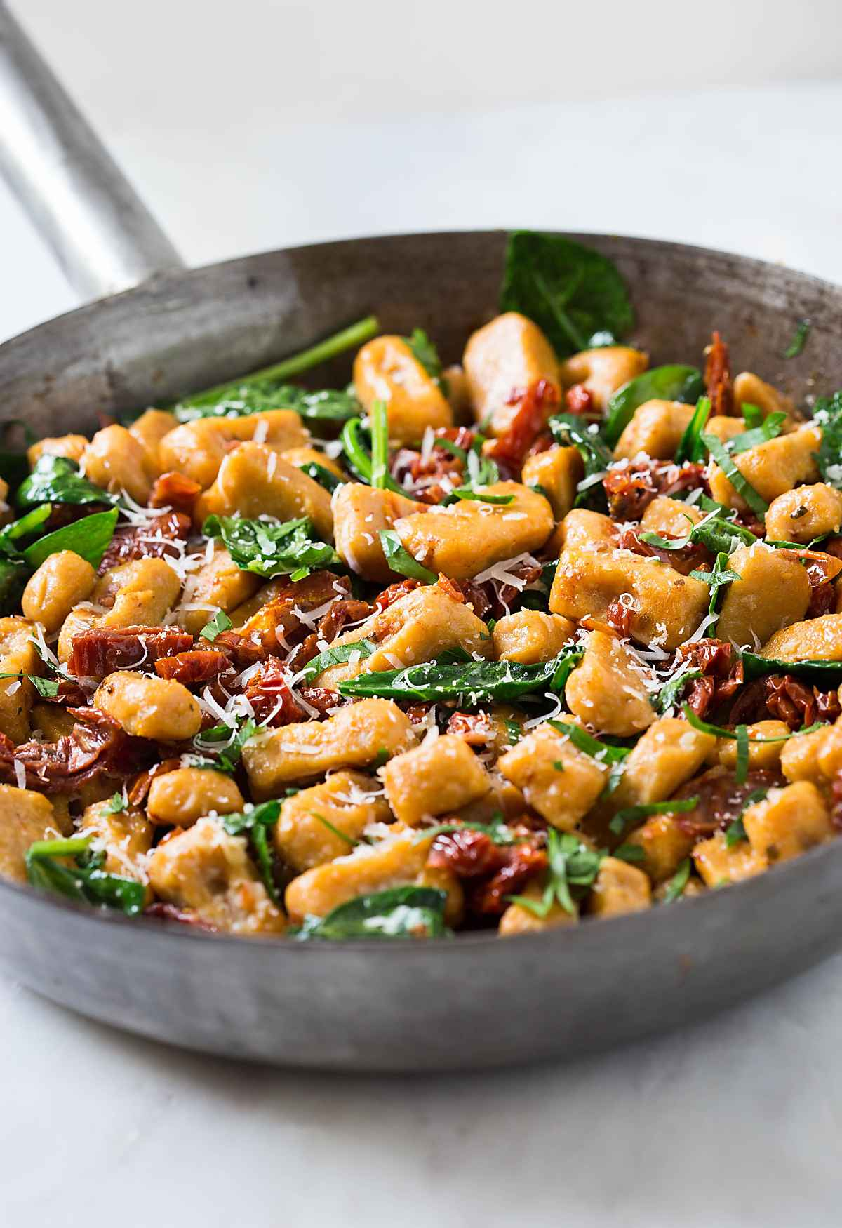 Stir-fry sweet potato gnocchi with spinach and sun-dried tomatoes to make the easiest dinner
