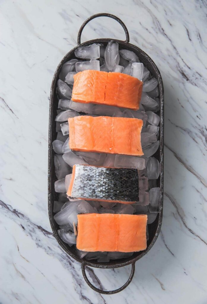 raw salmon fillets are spread over ice cubes in a tray