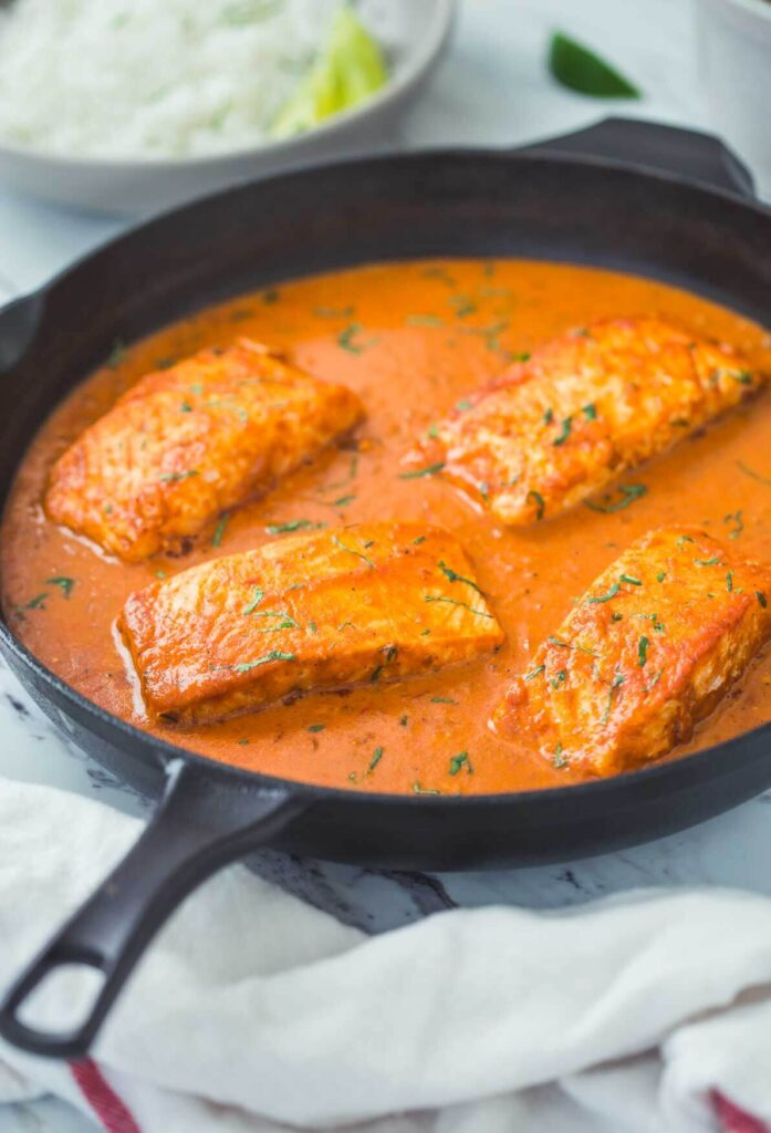 Ready to serve Indian salmon curry with coconut in cast iron skillet