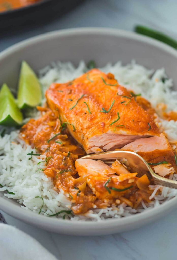 Indian salmon curry with coconut served in a deep plate with white rice and lemon wedges on the side.