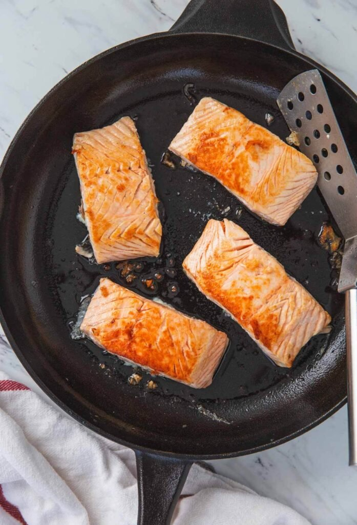 process of searing salmon fillets in a large cast iron skillets with stainless steel spatula.