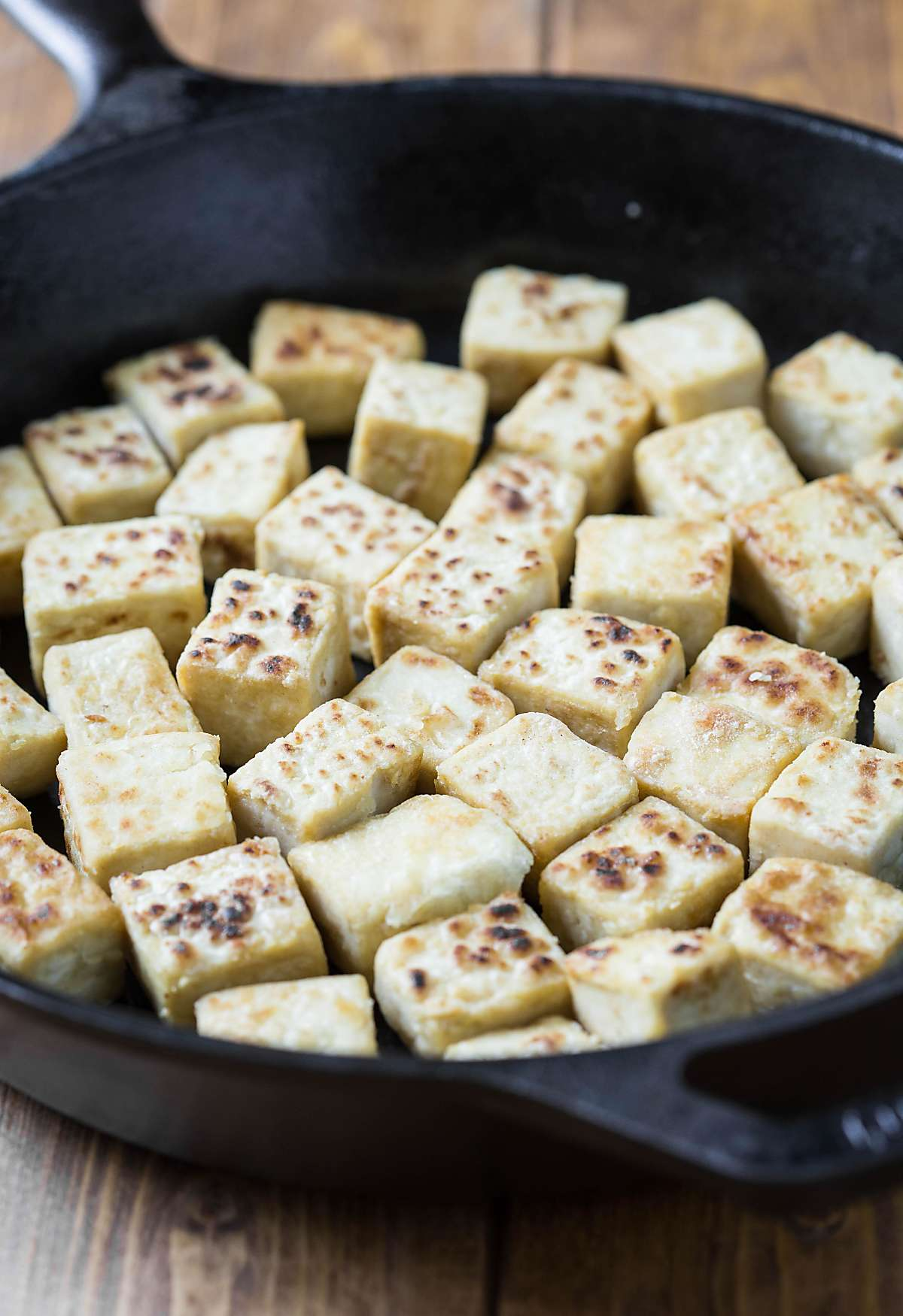 Cooking tofu in a cast iron skillet to form a crust.