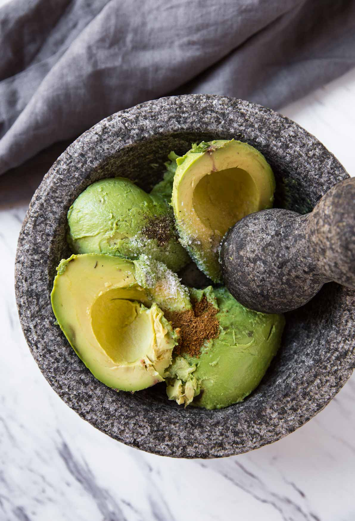 Peeled and pitted avocados in the molcajete for making fresh and healthy guacamole