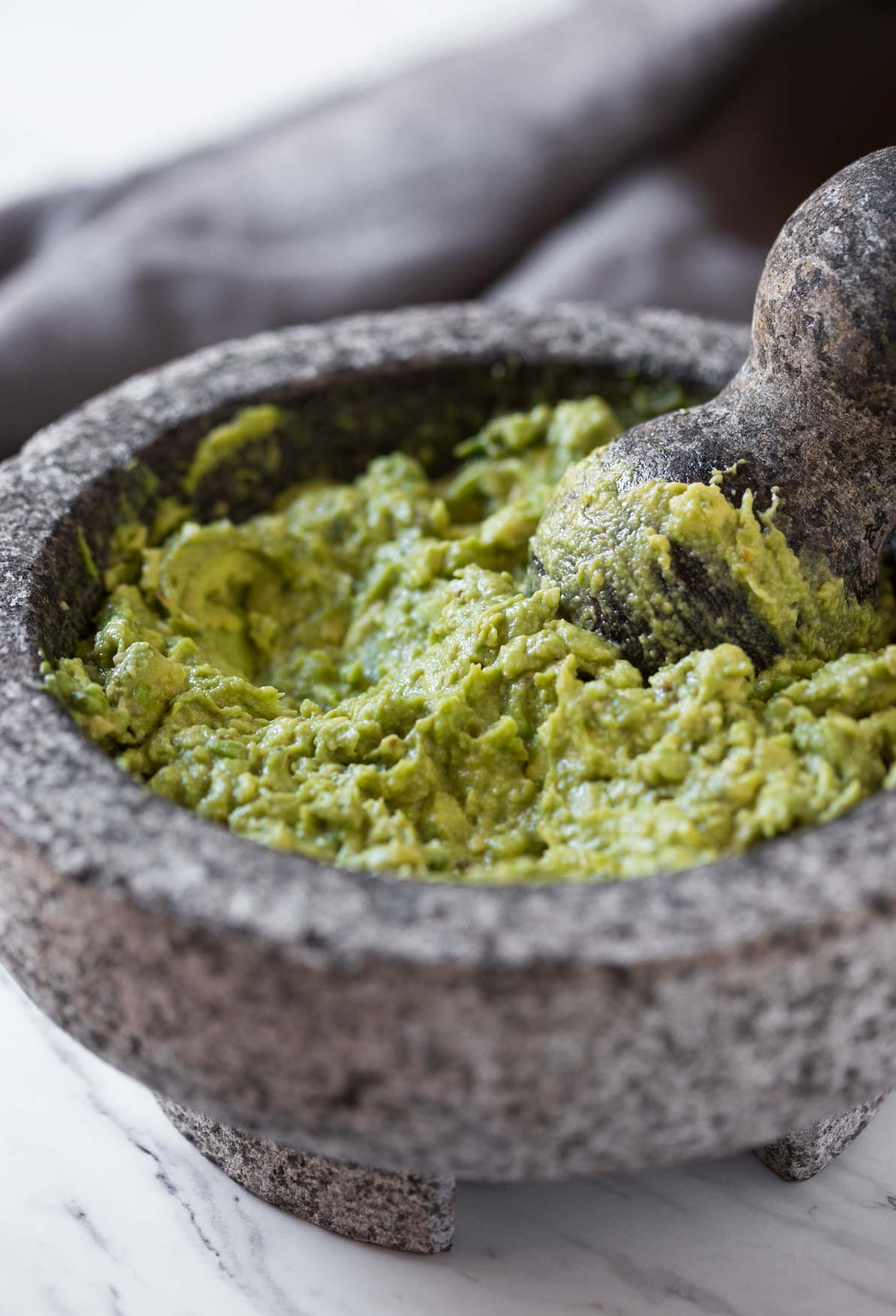 Mashed chunky avocados in the molcajete for making fresh and healthy guacamole