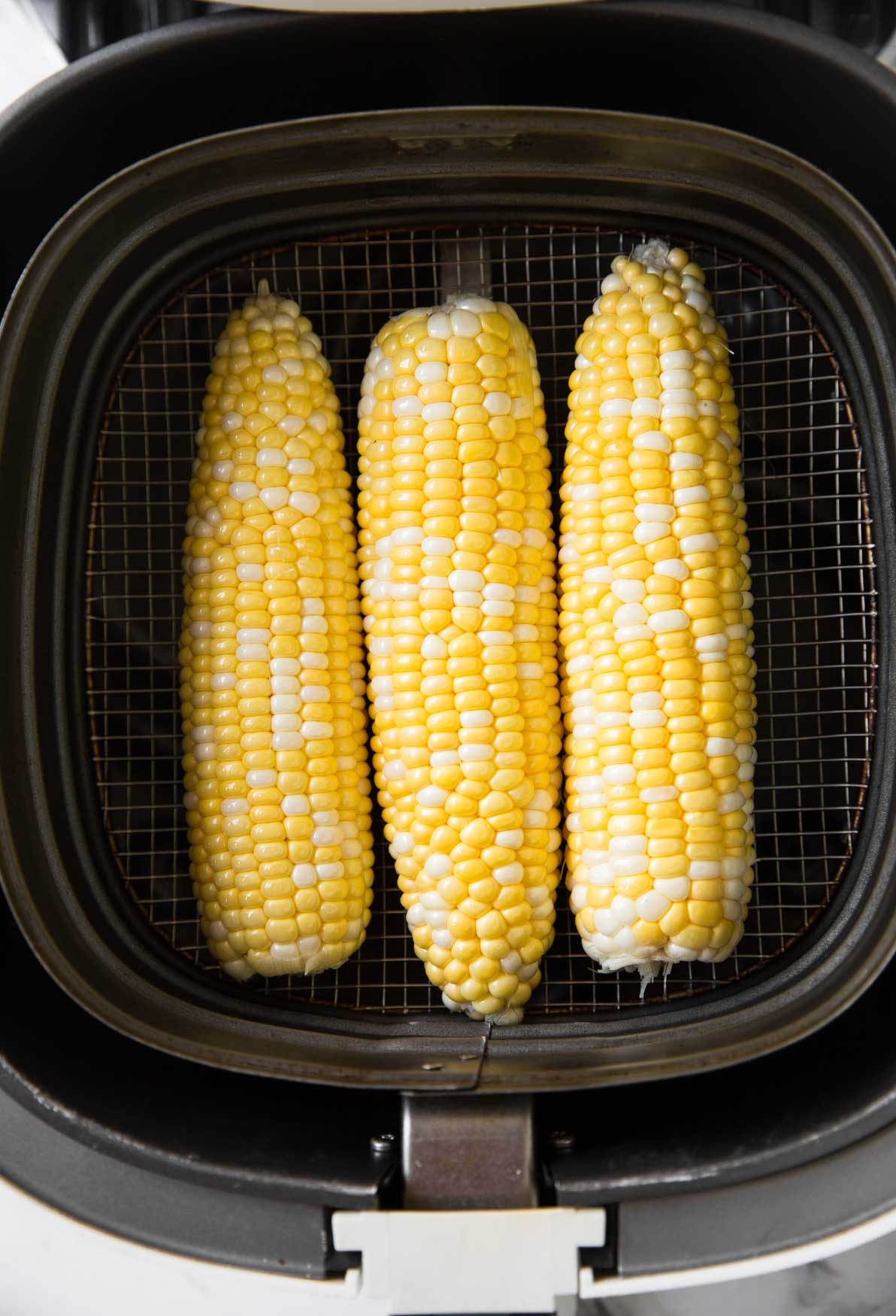Corn on the cob placed in Air Fryer Basket.