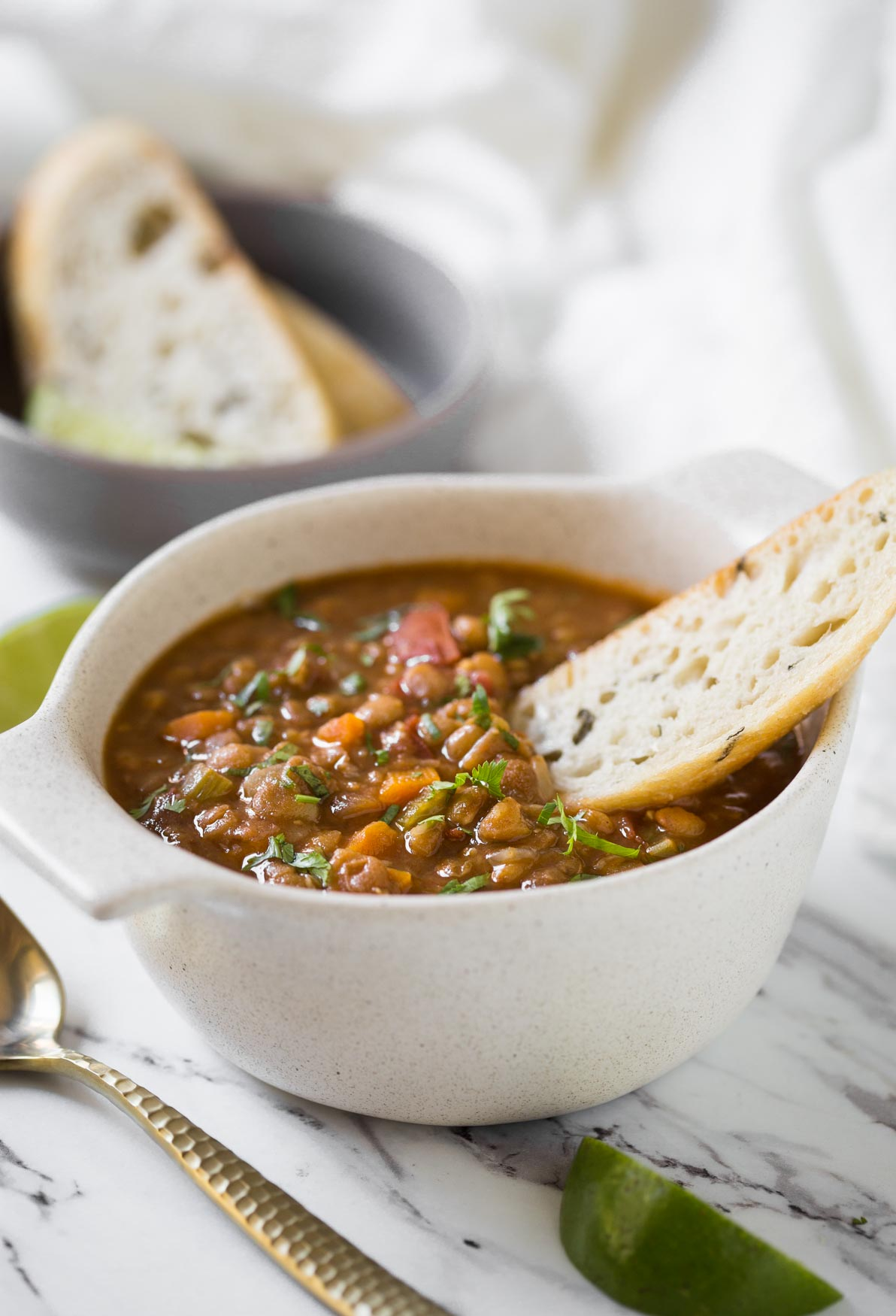 Whole lentil soup in bowl with bread