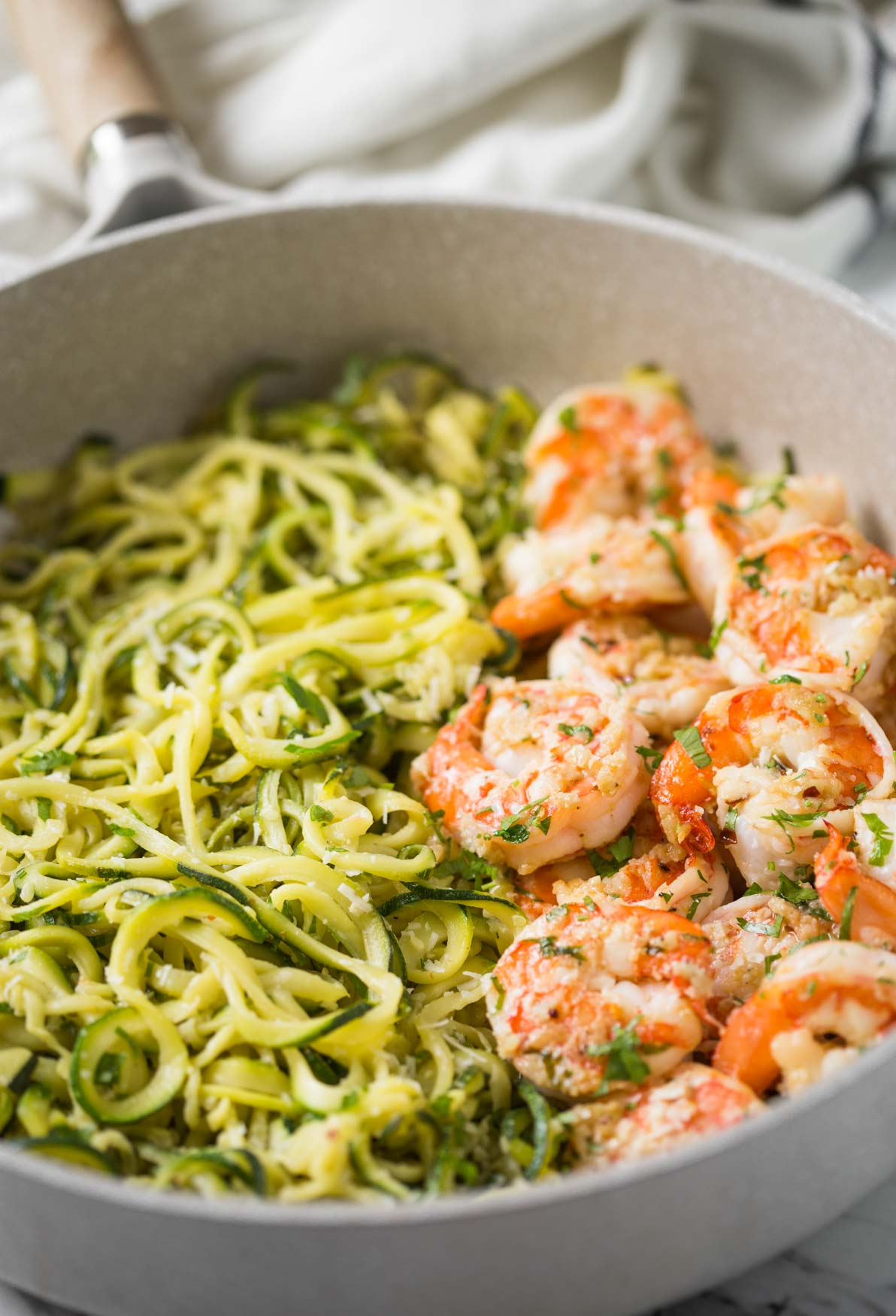 Shrimps and zucchini noodles cooked in fresh garlic and lemon juice and topped with finely chopped fresh herbs