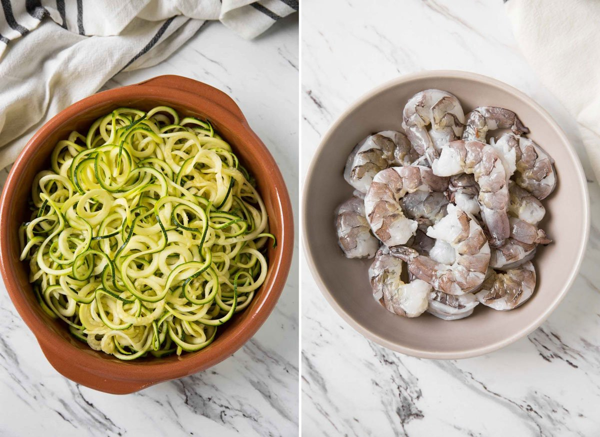 Zucchini noodles and raw shrimp in a bowl for making garlic shrimp and zucchini pasta.