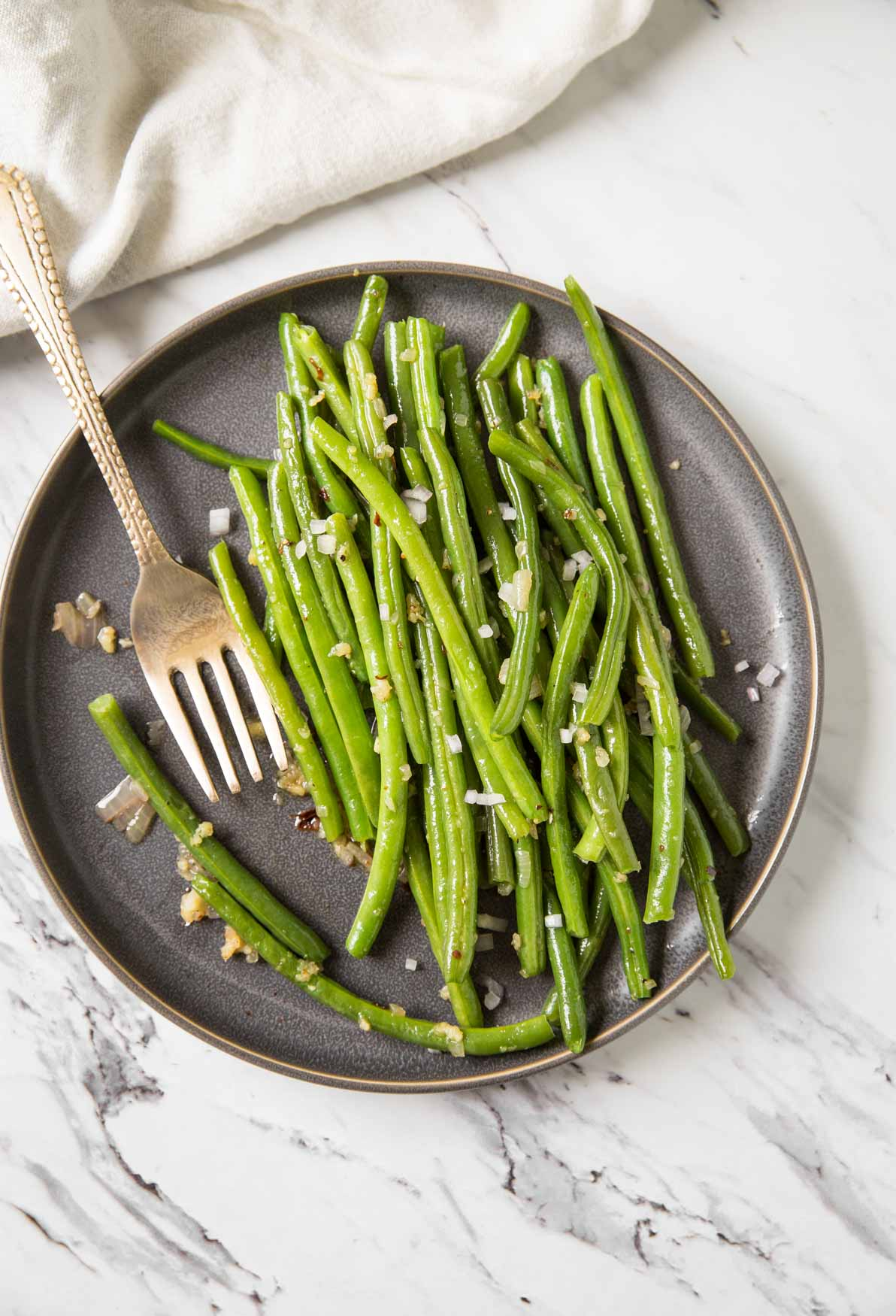 Sauteed garlic green beans in a serving plate with spoon