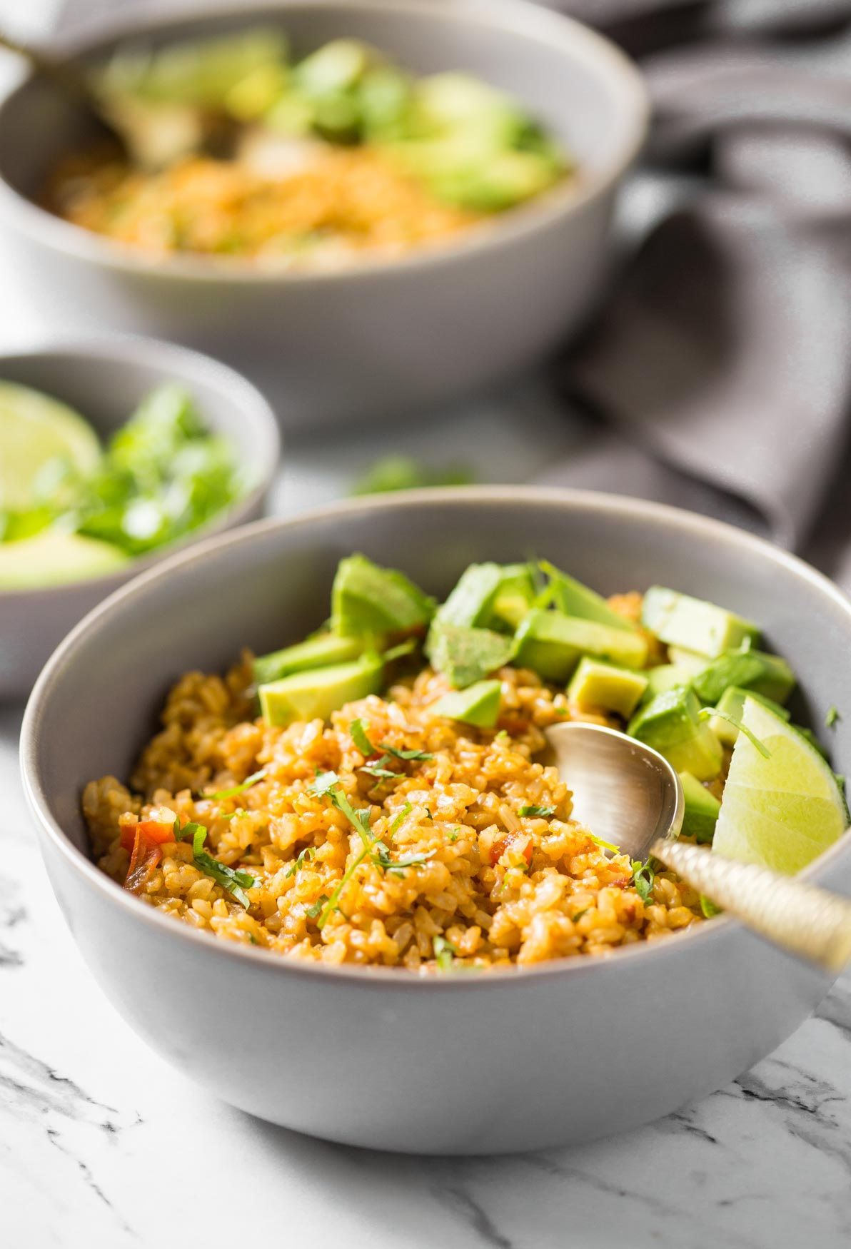 Mexican brown rice in a bowl with avocados, lime, and a spoon