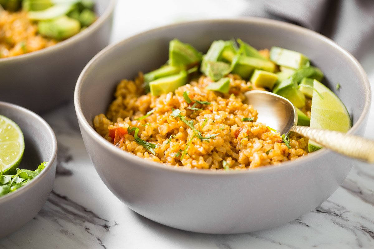 Mexican rice in a bowl with avocados, lime, and a spoon