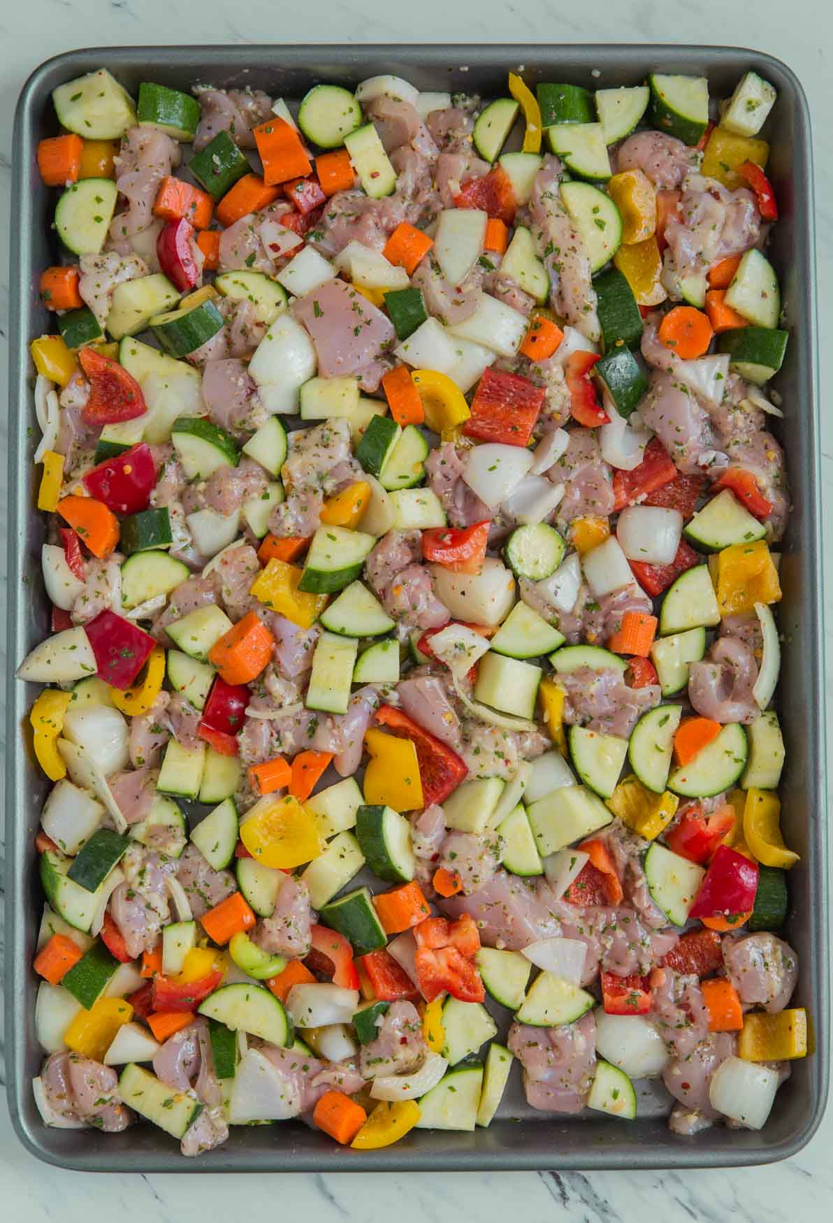 Marinated chicken and vegetables in a baking tray ready to go in the oven