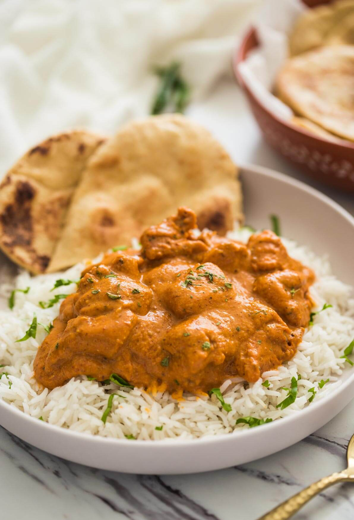 Restaurant style chicken tikka masala ready to serve in serving plate with homemade naan bread and plain rice