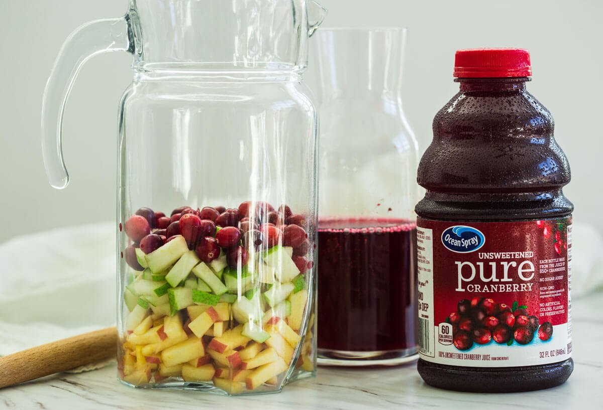 fresh diced fruits in a pitcher and fresh cranberry juice for making healthy cranberry sangria