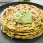 Healthy zucchini pancakes stacked in a serving plate with a dollop of green avocado sauce