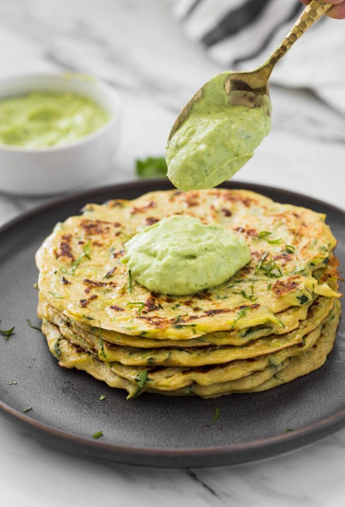 Healthy zucchini pancakes stacked in a serving plate