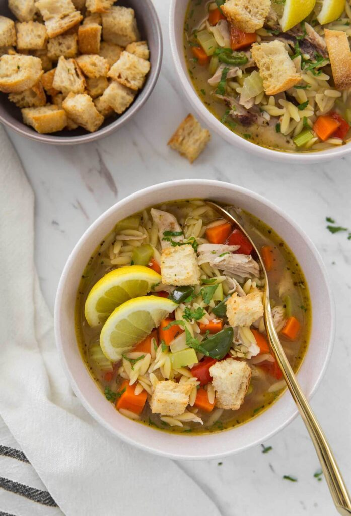 Healthy lemon chicken soup with orzo in a serving bowl with some croutons on the side.