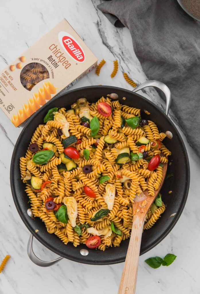 Healthy Mediterranean Pasta with artichoke, olives, and tomato in a large skillet
