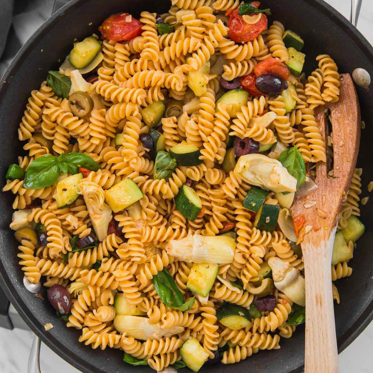 Healthy Mediterranean pasta with artichokes and olives in a large skillet with a wooden spatula.