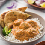 Butter chicken meatballs in a serving dish with naan bread, plain rice, lime wedge and green chili on the side.